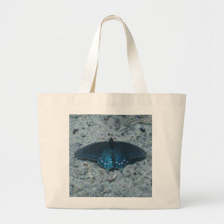 blue and black butterfly on sandy beach canvas bag