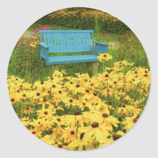 Blue bench in a field of  yellow black-eye Susans. Classic Round Sticker