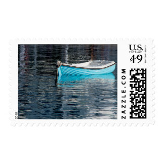 Blue fishing boat with reflection postage stamp