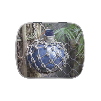 blue glass bottle faded in net against fence jelly belly candy tins
