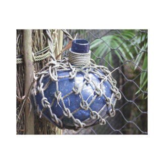 blue glass bottle faded in net against fence canvas print