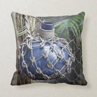blue glass bottle faded in net against fence throw pillow