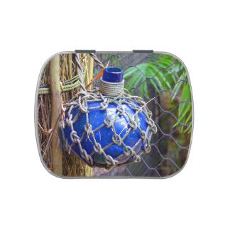 blue glass bottle in net against fence jelly belly candy tin