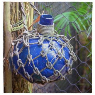 blue glass bottle in net against fence napkin