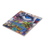 """Blue graffiti evil eye tile<br><div class=""""desc"""">Colorful distressed modern  urban graffiti photo on a city wall,  in Prague with a blue evil eye and multicolored graffitied words and text.</div>"""