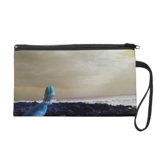 blue hand holding barnacle yellow sky wristlet clutches