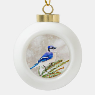 Blue jay in a pine tree with snow ceramic ball christmas ornament