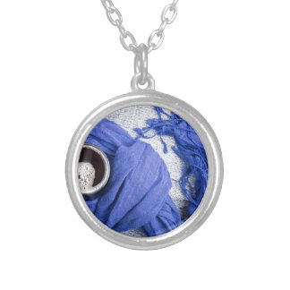 Blue scarf tied around the mug with hot coffee silver plated necklace