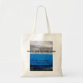 Blue sea, black and white sky tote bag