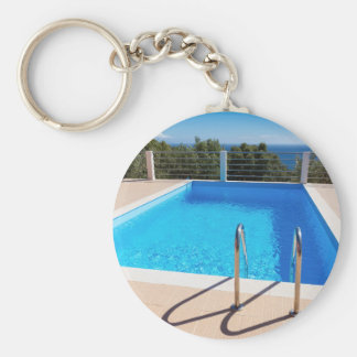 Blue swimming pool with steps at sea keychain