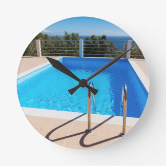 Blue swimming pool with steps at sea round clock