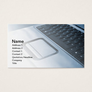 blue toned photo of a laptop keyboard and mousepad business card