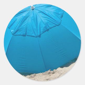 blue umbrella at the beach classic round sticker