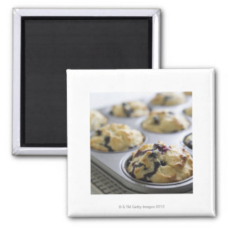Blueberry muffins in a baking tin on a cooling magnet