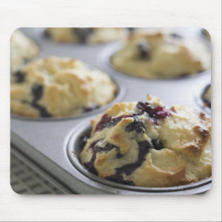 Blueberry muffins in a baking tin on a cooling mouse pad