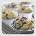 Blueberry muffins in a baking tin on a cooling square sticker