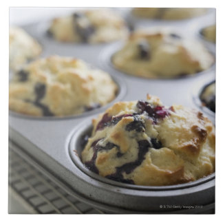 Blueberry muffins in a baking tin on a cooling tile