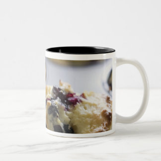 Blueberry muffins in a baking tin on a cooling Two-Tone coffee mug
