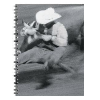 Blurred shot of cowboy wrestling steer spiral note book