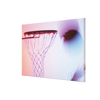 Blurred view of basketball going into hoop canvas print
