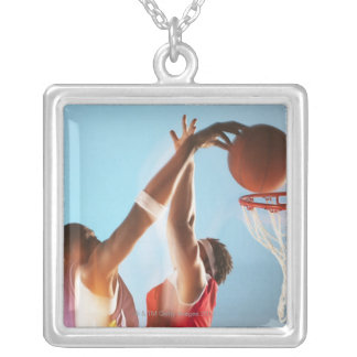 Blurred view of basketball player dunking silver plated necklace