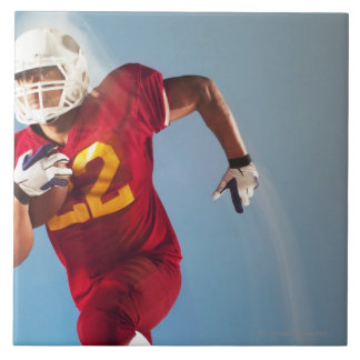 Blurred view of football player running with ceramic tile