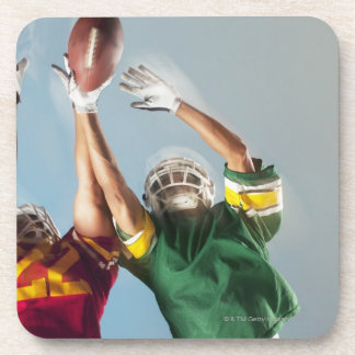 Blurred view of football players reaching for coaster