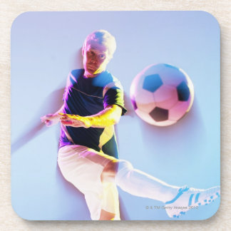 Blurred view of soccer player kicking ball 2 drink coaster