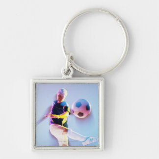Blurred view of soccer player kicking ball 2 key chains