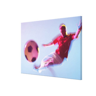 Blurred view of soccer player kicking ball gallery wrap canvas