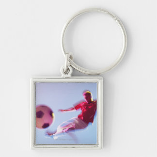 Blurred view of soccer player kicking ball keychains