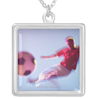Blurred view of soccer player kicking ball silver plated necklace