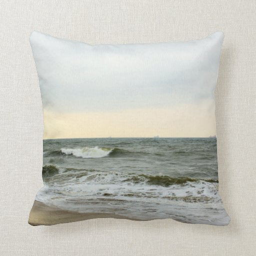 Boats and surge from the border of the beach throw pillows