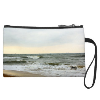 Boats and surge from the border of the beach suede wristlet