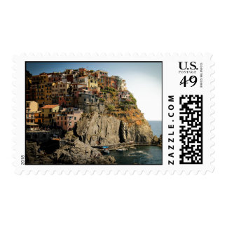 Boats in harbor and houses on the hill postage stamp