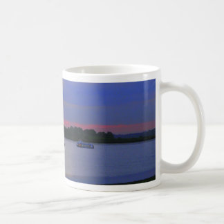Boats passing on the river at sunset coffee mug
