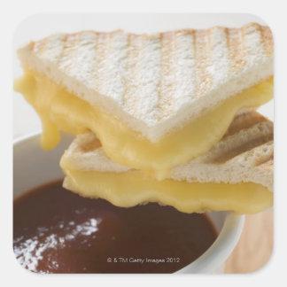 Bocadillos tostados del queso y una taza de sopa colcomanias cuadradass