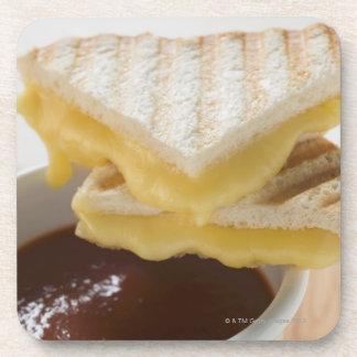 Bocadillos tostados del queso y una taza de sopa posavasos de bebidas