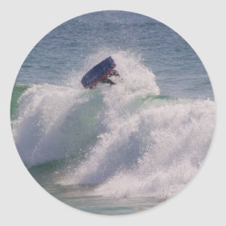 Body boarder riding a big wave classic round sticker
