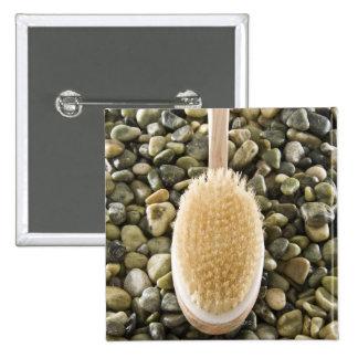 Body scrub brush on rocks pinback button