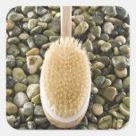 Body scrub brush on rocks square sticker