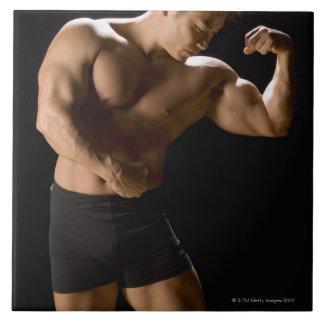 Bodybuilder masculino que dobla los músculos, azulejo cuadrado grande