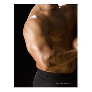 Bodybuilder masculino que dobla los músculos, postal