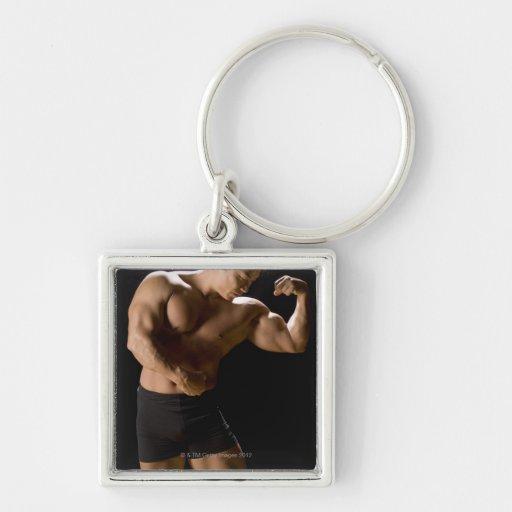 Bodybuilder masculino que dobla los músculos, vist llaveros