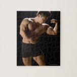 Bodybuilder masculino que dobla los músculos, vist rompecabeza