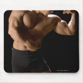 Bodybuilder masculino que dobla los músculos, vist alfombrillas de ratón
