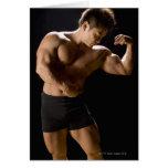 Bodybuilder masculino que dobla los músculos, vist felicitaciones