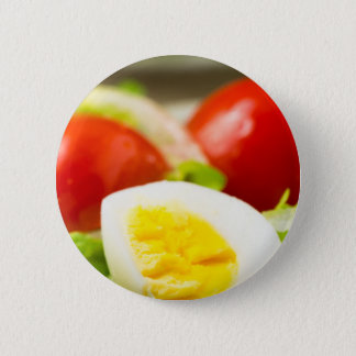 Boiled egg on a plate with lettuce, onions pinback button