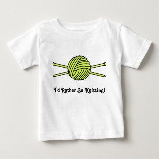 Bola amarilla del hilado y de las agujas que hacen playera de bebé