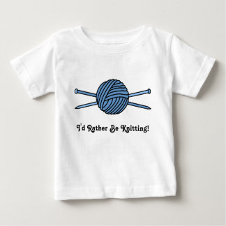 Bola azul del hilado y de las agujas que hacen playera de bebé